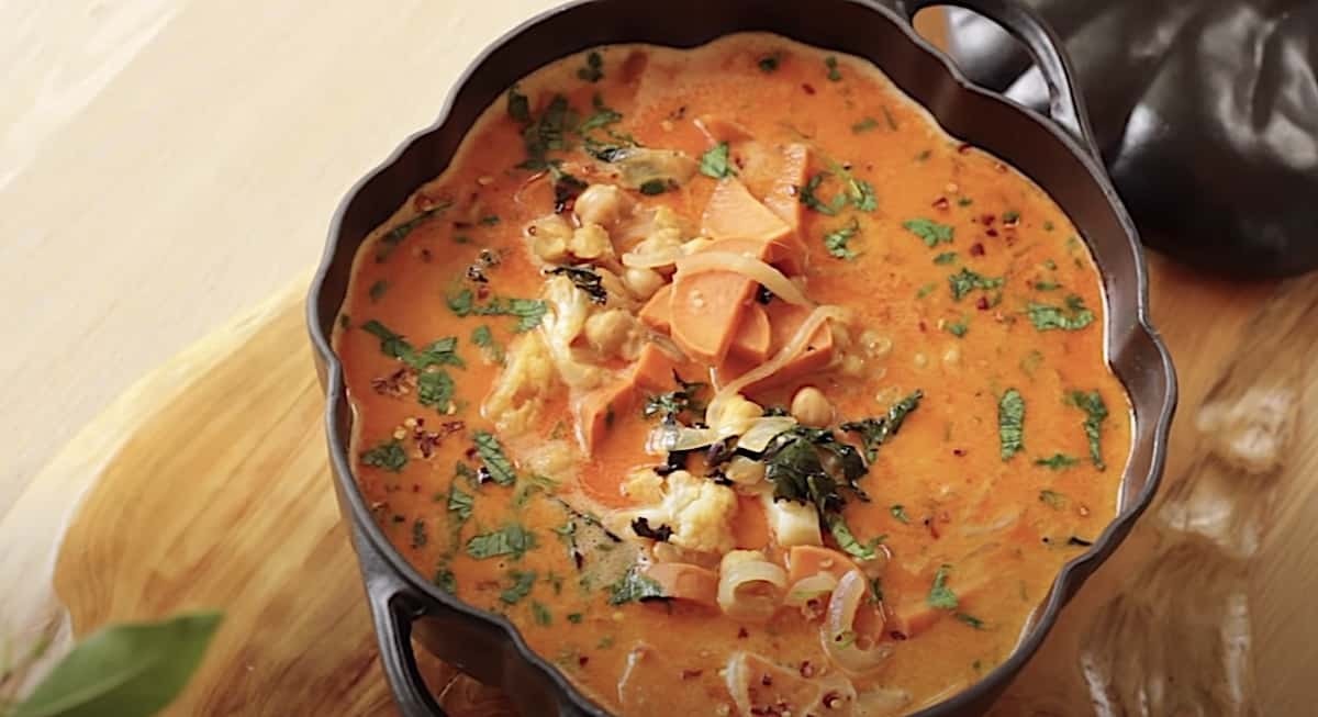 an overhead shot of a Thai red curry in a pumpkin tureen