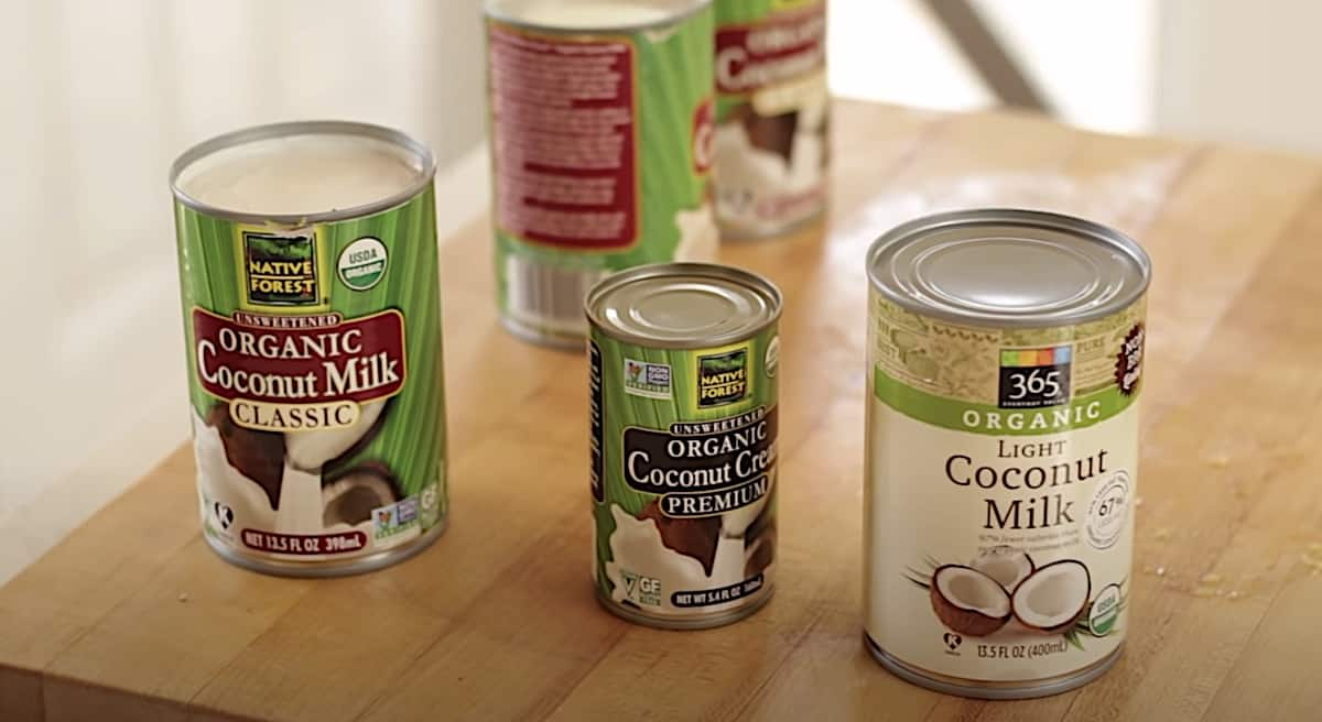 a collection of various styles of coconut milk in cans on a cutting board
