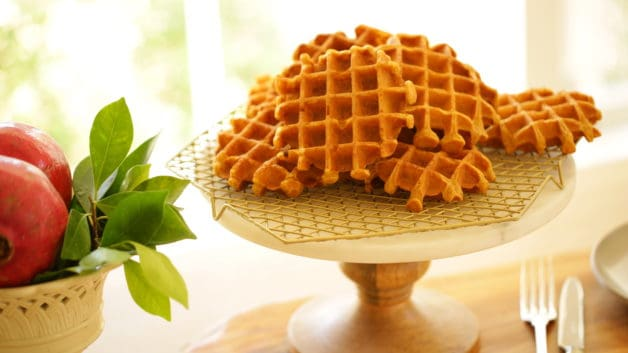 a marble cake stand with a gold cooling rack stacked with freshly baked pumpkin waffles
