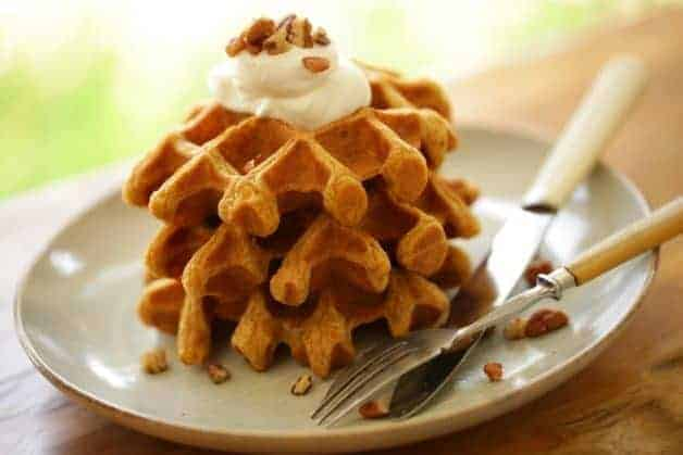 Pumpkin Spice Waffles stacked on a plate topped with whipped cream and chopped pecans