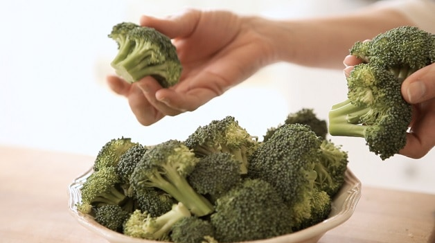 A person holding a piece of broccoli
