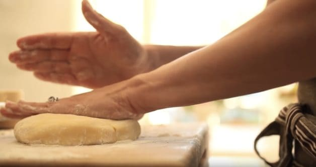 Pressing down tart dough on a floured cutting board