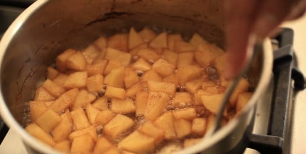 Apple chunks cooking in a pot with cinnamon for an apple compote