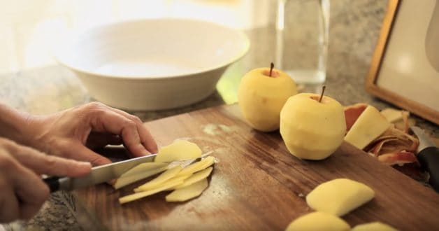 Slicing apples paper thin on a cutting board for a French Apple Tart Recipe