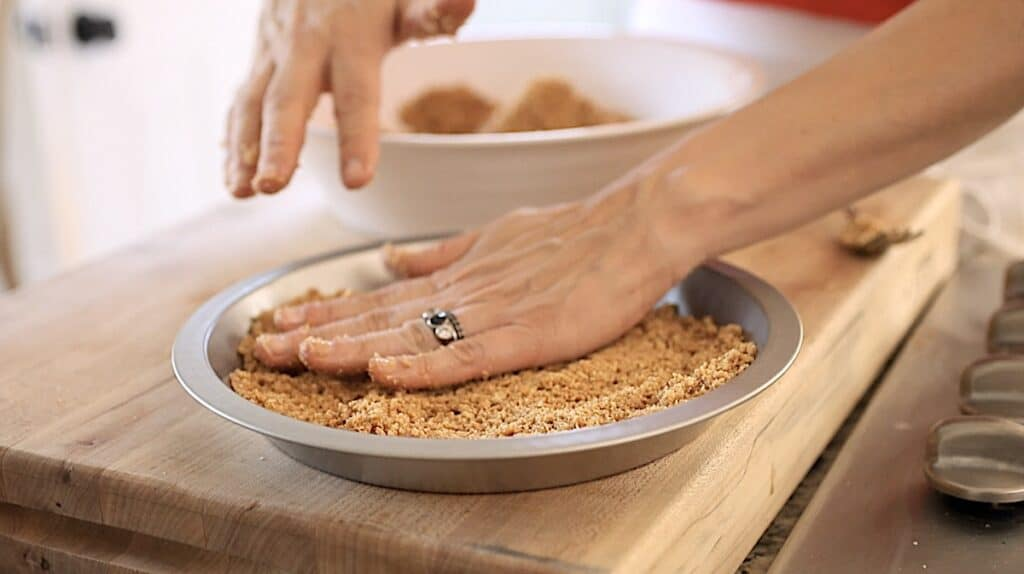 a hand patting down graham cracker crumbs in a metal pie plate