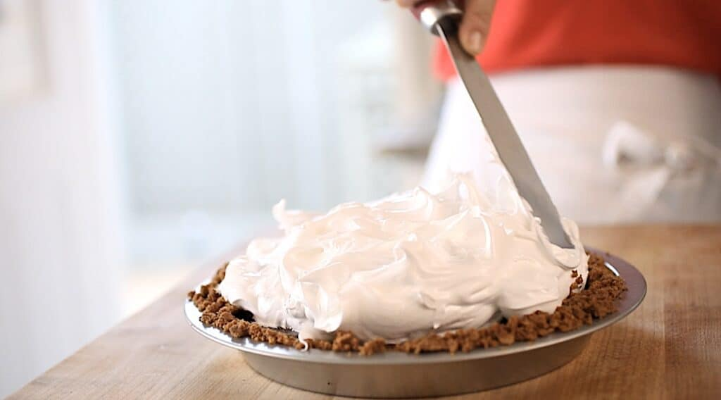 a metal spatula spreading marshmallow topping on a pie