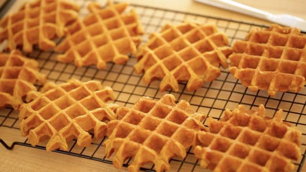 Freshly baked pumpkin waffles on a cooling rack
