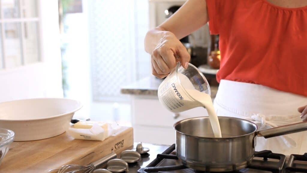 pouring heavy cream into a sauce pot