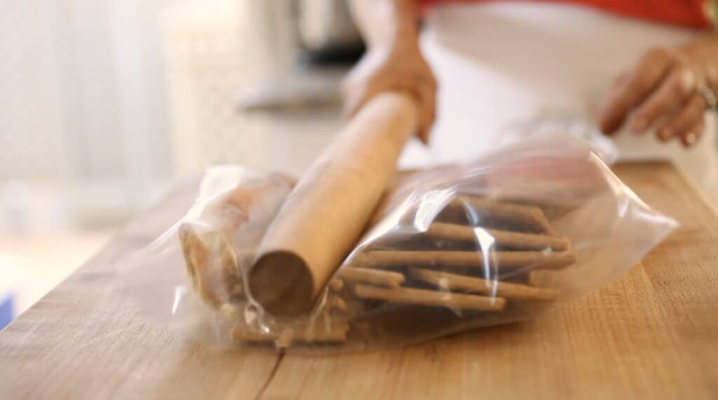 a person whacking graham crackers in a Ziploc bag with a rolling pin