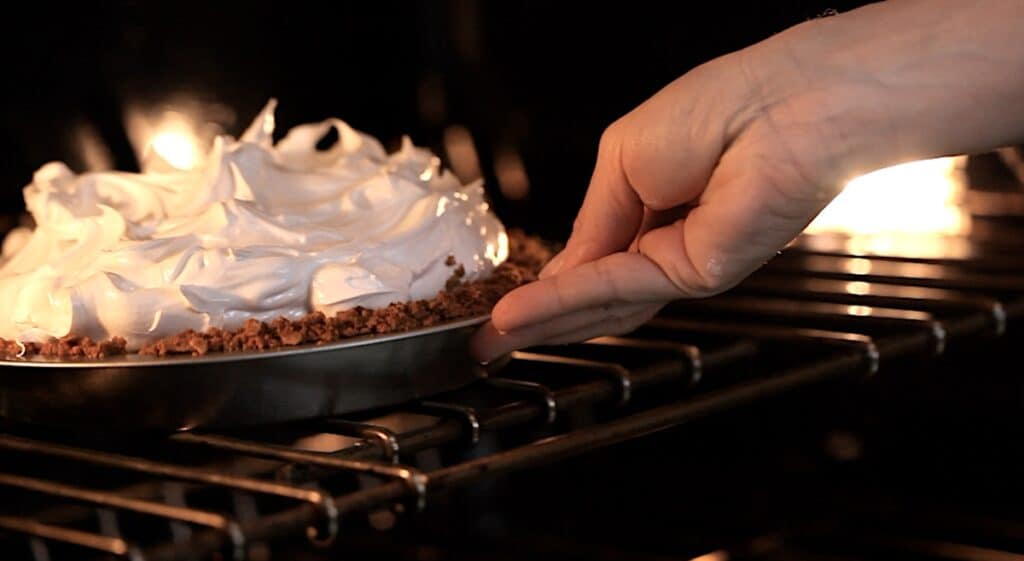 Hand Placing S'more Pie in the oven to toast the marshmallow topping