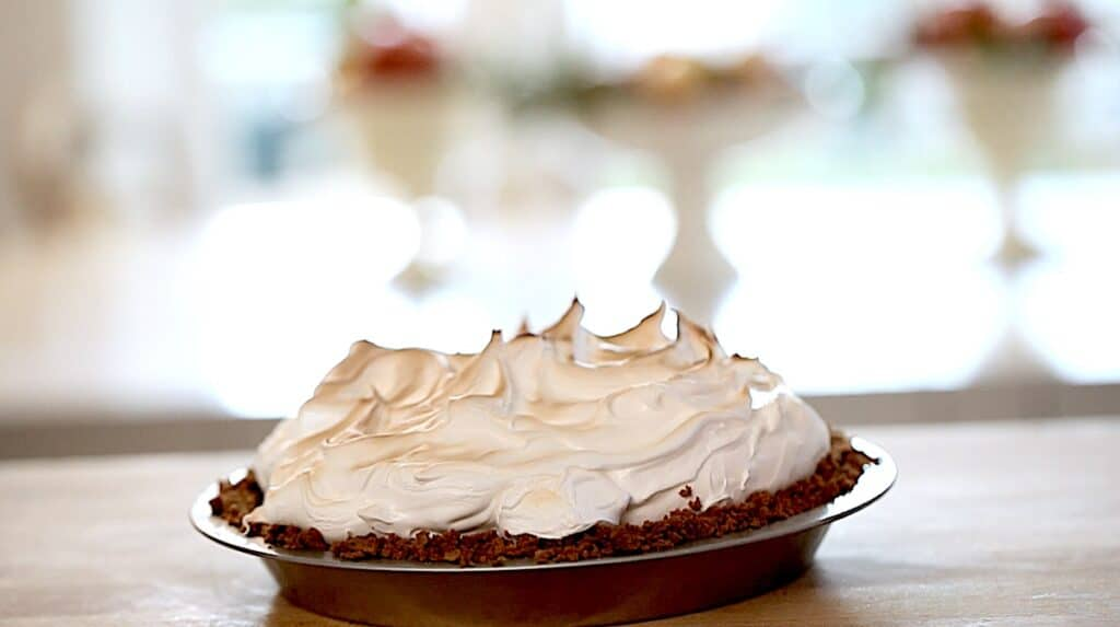 A toasted S'More Pie cooling on a countertop