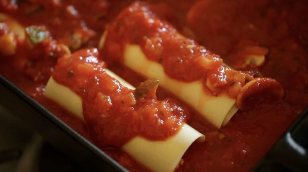Veggie Lasagna Roll Ups in a bed of tomato sauce ready for the oven