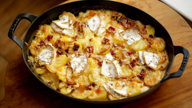 Easy Tartiflette Recipe served in an oveal gratin pan, overhead shot.