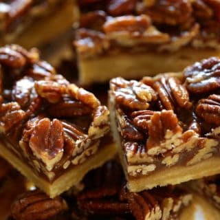 Pile of sliced pecan bars on a cake stand