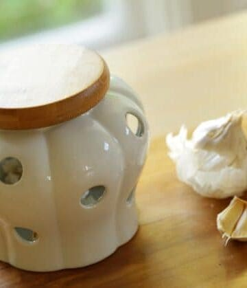 Ceramic Garlic Keeper with wooden top with a garlic clove beside it
