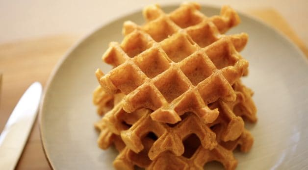 Waffles piled on a plate made with an all clad waffle iron. One of 15 gifts for Foodies