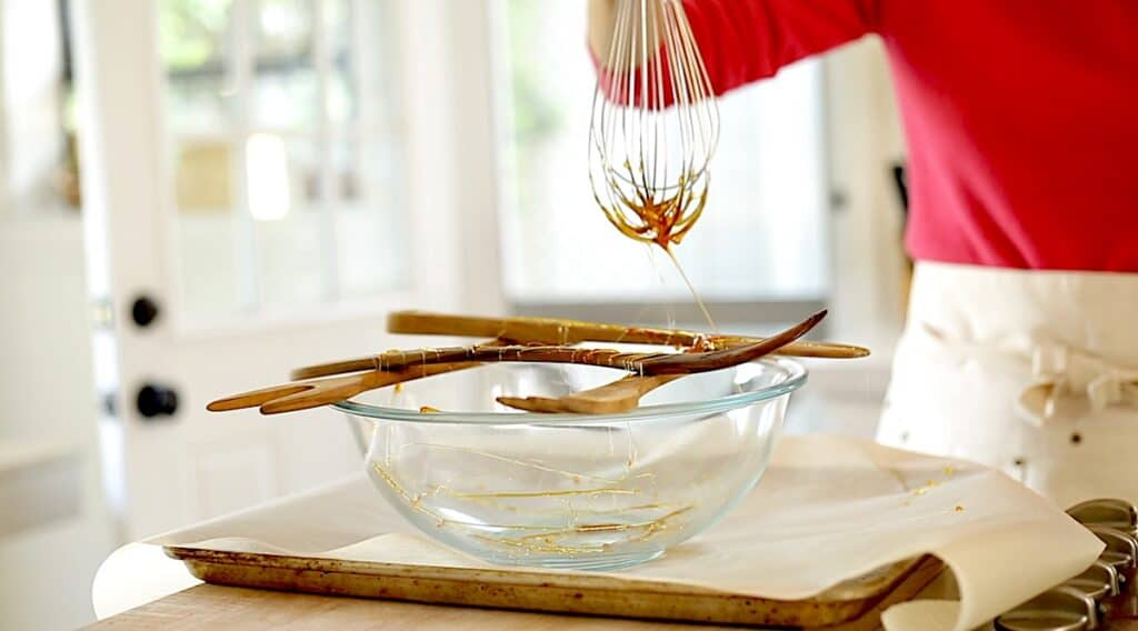 a person moving a whisk dipped in hot caramel across wooden spoons