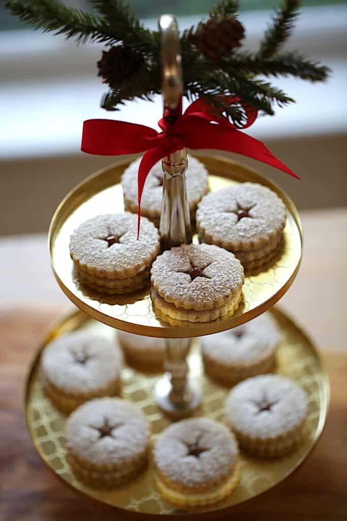 Linzer Cookies on a 2-tiered gold cake stand