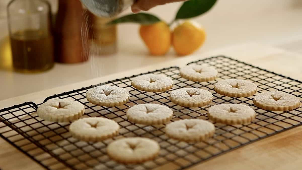 linzer cookie tops being dusted with powdered sugar