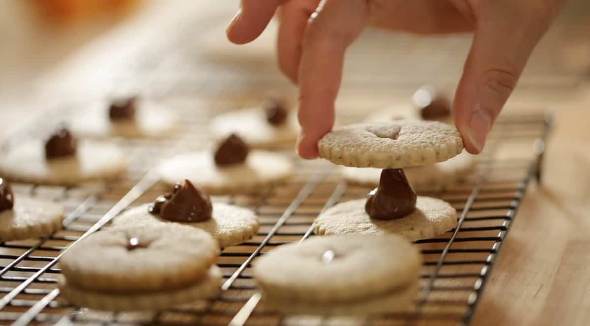 a person adding linzer cookie tops to a cookie bottom with Nutella in the center