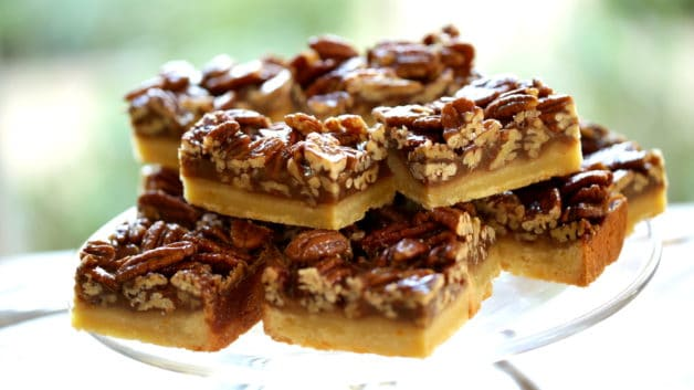 Pile of sliced pecan bars sliced into rectangles on a glass cake stand