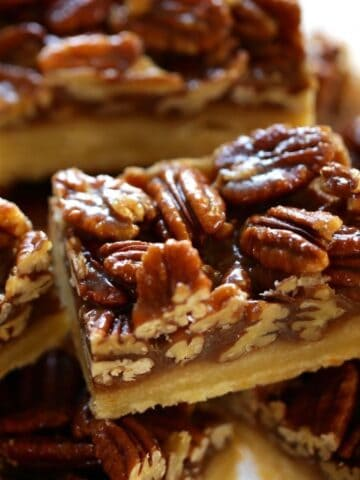 Pecan Bars with Shortbread Crust sliced into bars on a cake stand