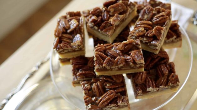 Overhead shot of sliced pecan bars on a cake stand