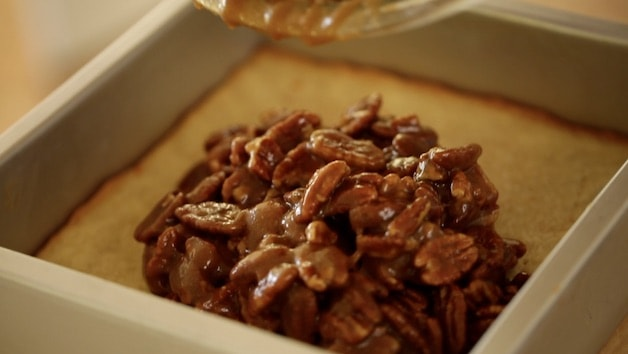 pouring pecan filling into shortbread crust
