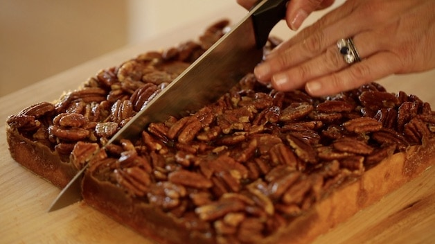 Slicing freshly baked pecan bars on a cutting board