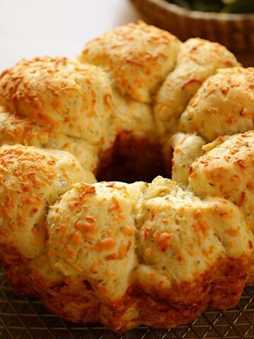Savory Monkey Bread with Cheese on Top on a cooling rack