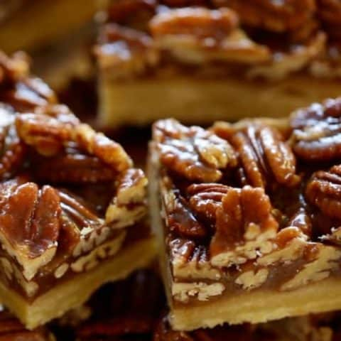 Sliced pecan bars piled on a glass cake stand