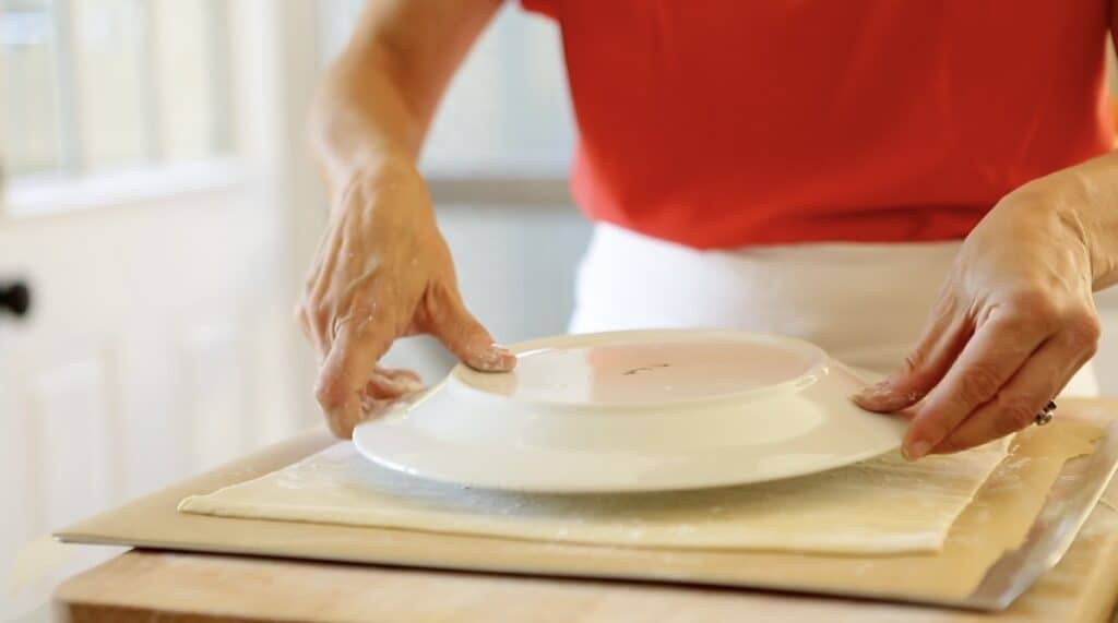 placing a dinner plate on a puff pastry round