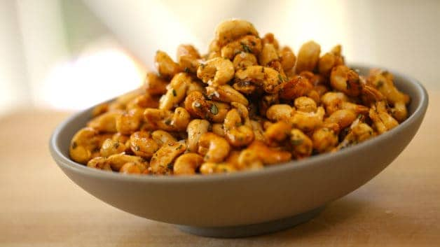 Bowl of honey glazed cashews garnished with fresh rosemary