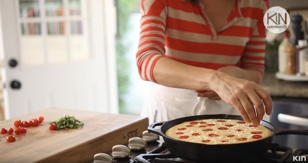 Adding Cherry Tomatoes to the top of a frittata in a skillet