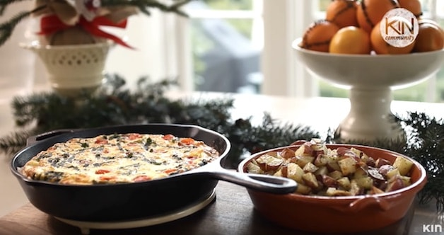 Frittata in a skillet served with roasted potatoes on a Christmas themed breakfast table