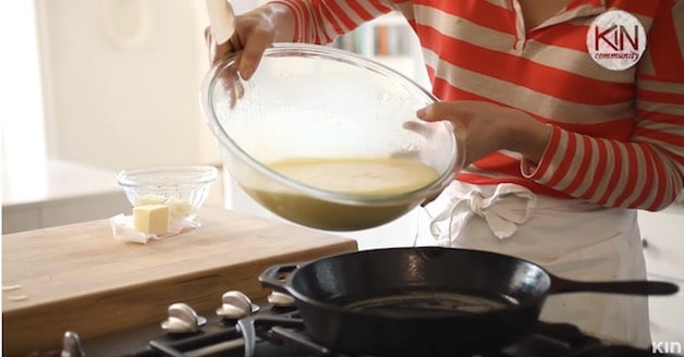 Egg batter being poured into a cast-iron skillet on a stovetop