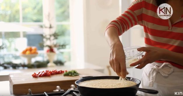 Adding cheese to an easy frittata recipe setting in a skillet on the cooktop