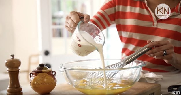 Heavy cream in pitcher added to eggs in a glass bowl