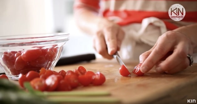 Cutting cherry tomatoes on a cutting board