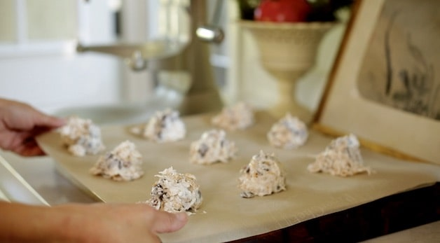 Cookie dough spooned out oto parchment lined cookie sheet