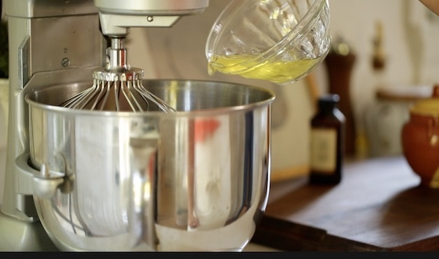 Bowl of egg whites being poured into the bowl of an electric mixer