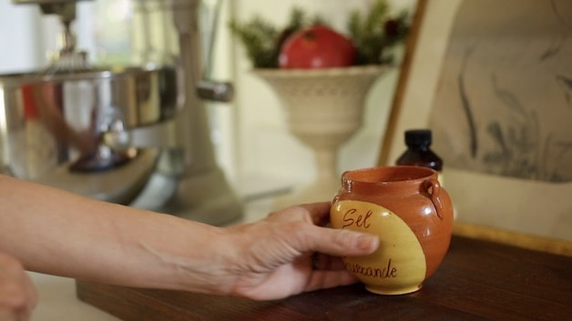 Hand reaching for salt pot to ad to egg whites in an electric mixer