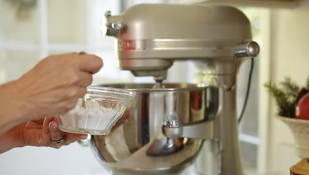 Adding spoonfuls of confectioner's sugar to a bowl of an electric mixer