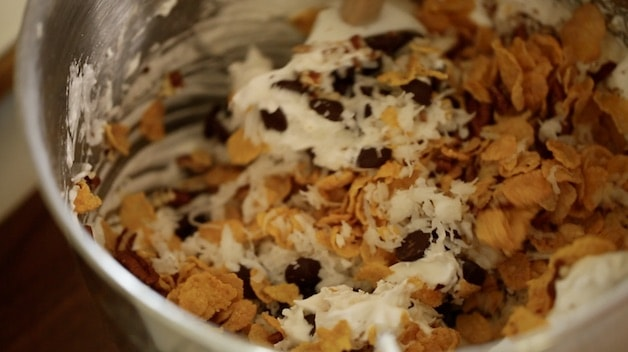 Bowl of stiff egg whites being mixed with chocolate chips, cornflakes, nuts and coconut