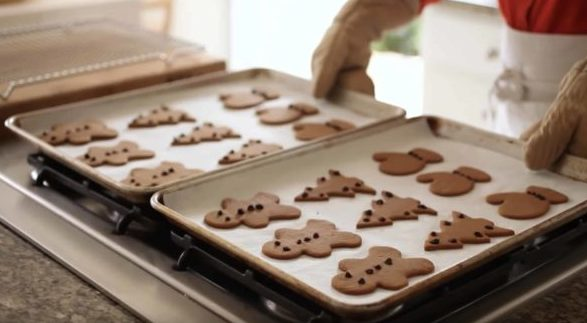 Trays of Gingerbread Cookies coming out of the oven on baking trays