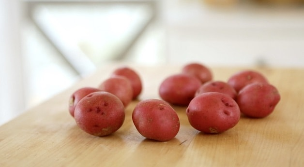 red potatoes on wood cutting board