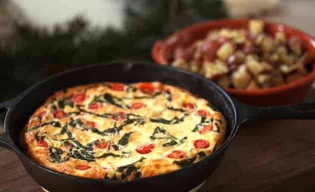Tomato, Basil and CHeese Frittata in a cast iron skillet with roasted potatoes in the background