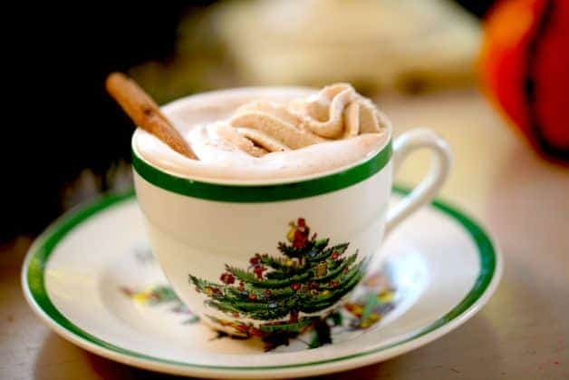 Gingerbread hot chocolate with whipped cream in Christmas themed cup and saucer
