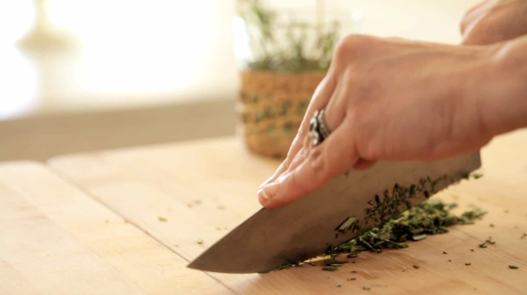 a person chopping rosemary on a board with a chef's knife