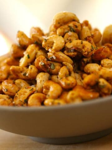 Honey Cashews with Rosemary Garnish in a Gray Bowl